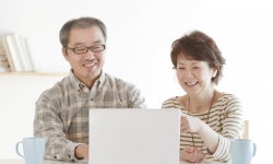 Japanese senior couple in front of Laptop